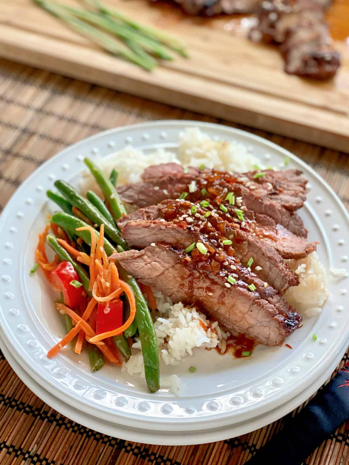 White plate filled with rice, green beansm and sliced asian steak.