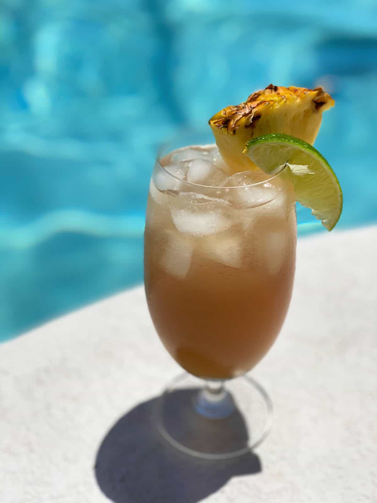 One glass of a cocktail next to a swimming pool garnished with a pineapple and lime.