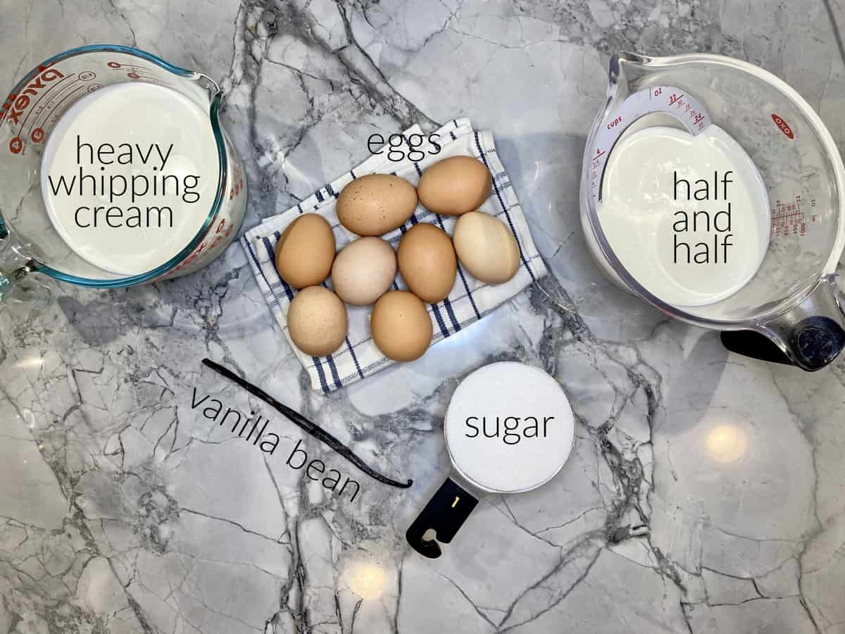 Ingredients on marble countertop: heavy whipping cream, eggs, vanilla bean, sugar, and half and half in measuring cup.