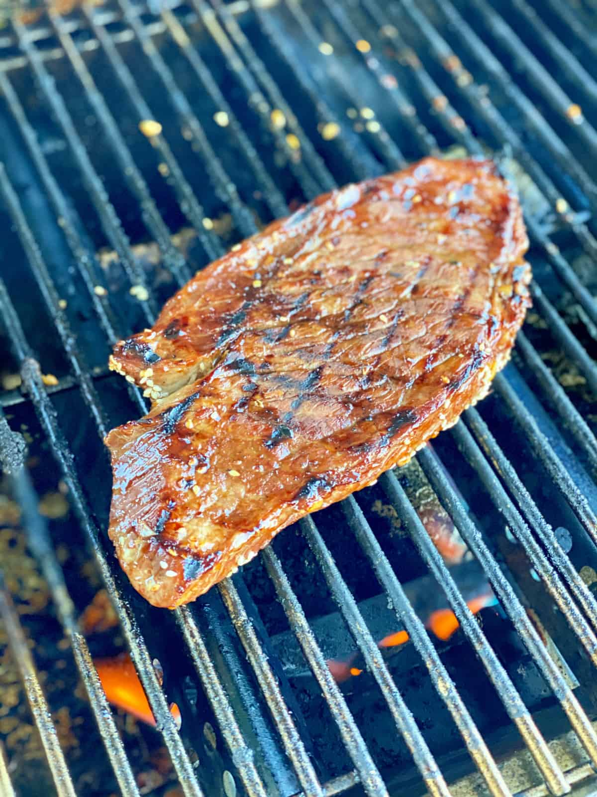 Large london broil steak with grill marks on top of a grill with fire underneath.