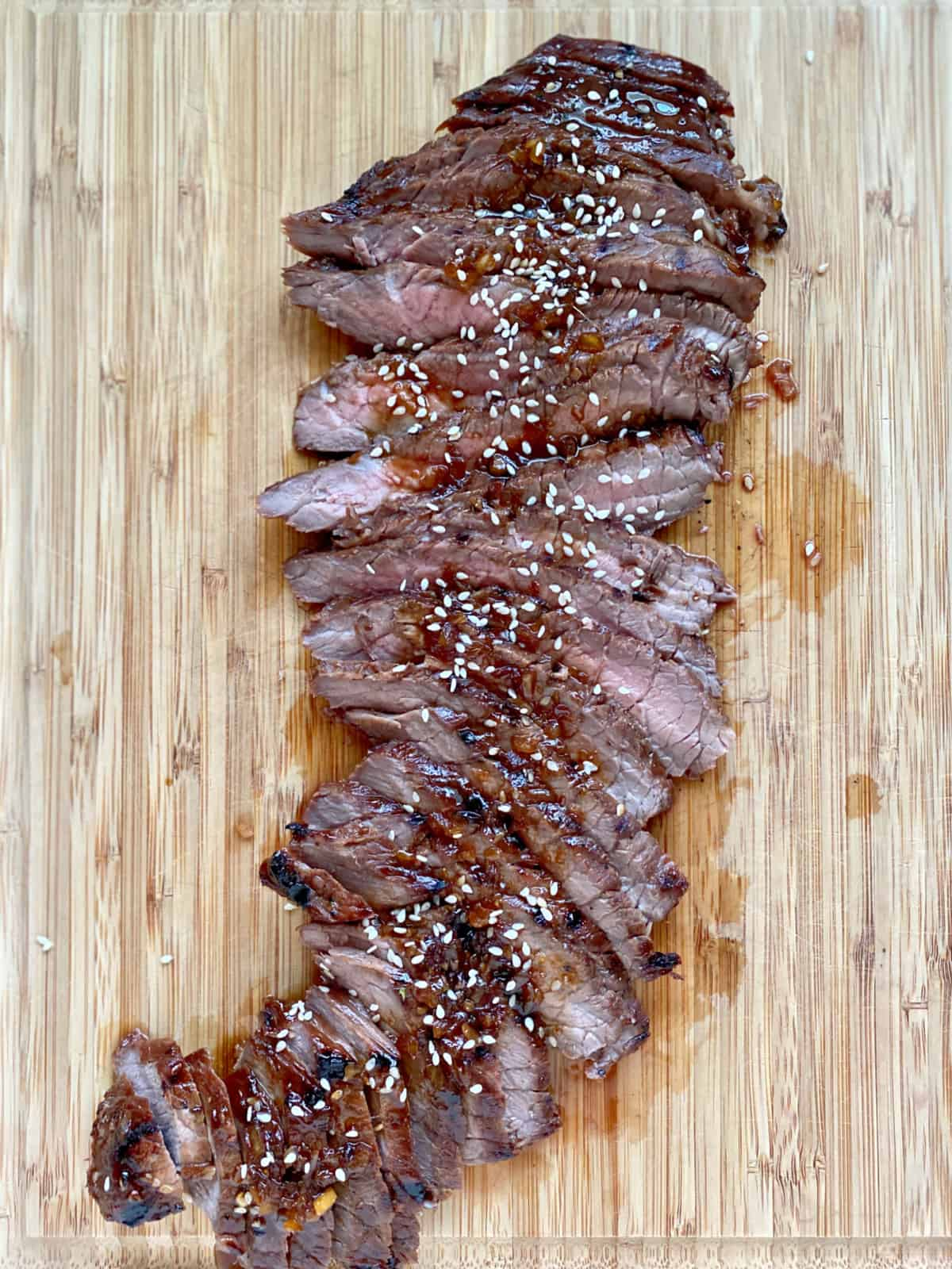 Top view of a wood cutting board with sliced steak topped with sauce and sesame seeds.