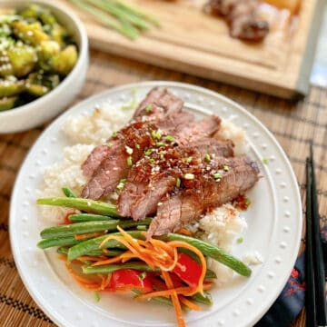 White plate filled with rice, green beans, carrots, bell peppers, and sliced steak with steak on a cutting board in the background.
