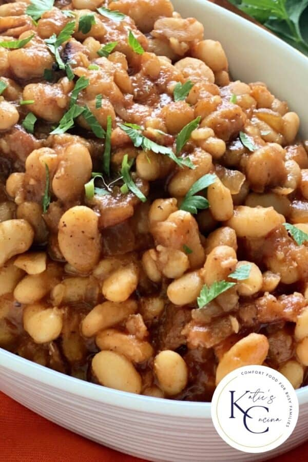 Close up of baked beans in a white oval bowl with logo on right corner.