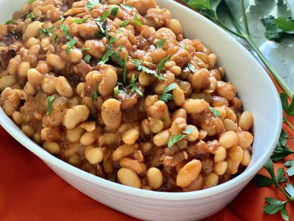 White oval bowl filled with baked beans with parsley on top.