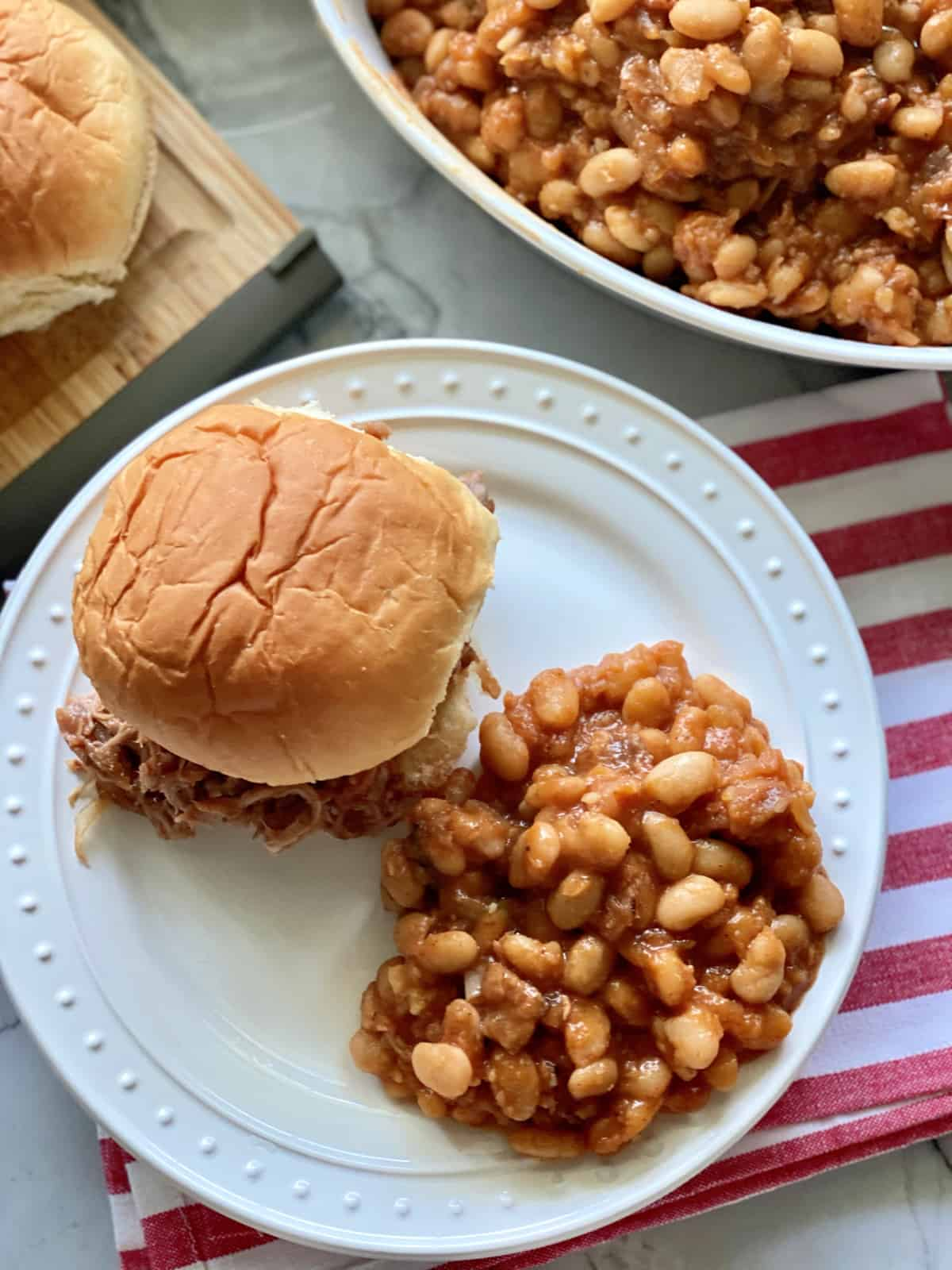 Top view of a white plate filled with baked beans and a pulled pork sandwich.