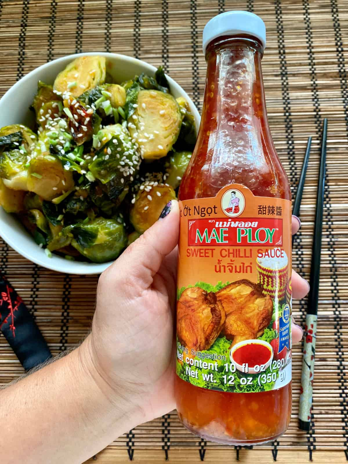 Female hand holding a bottle of Mae Ploy Sweet Chili Sauce.
