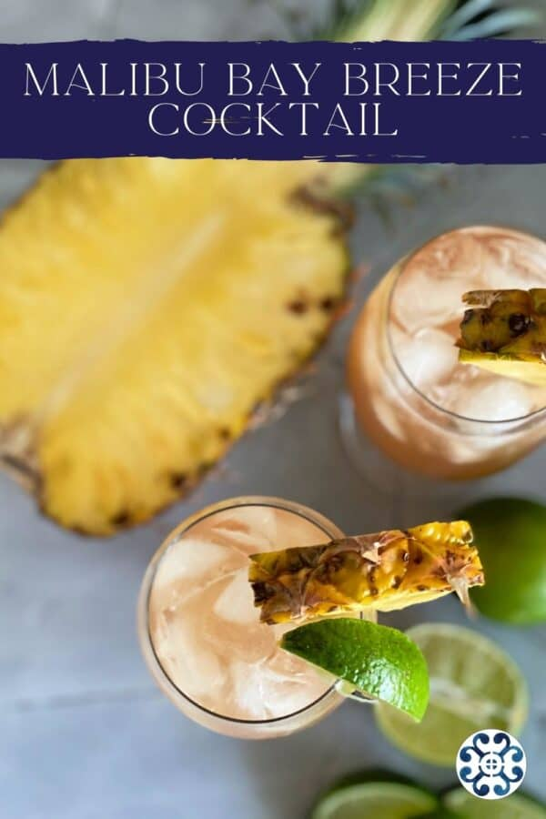 Top view of a cut pineapple with two glasses filled with a Bay Breeze Cocktail.
