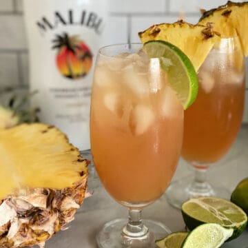 Two glasses filled with peach colored juice with limes and pineapple on counter.