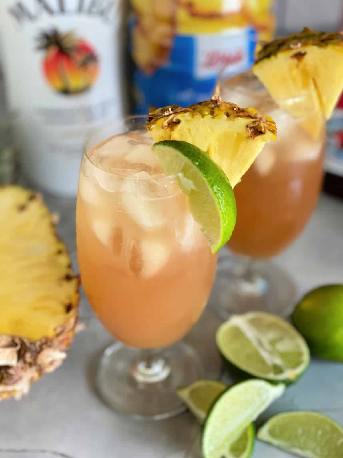 Two glasses of peach colored cocktails with pineapples and limes.