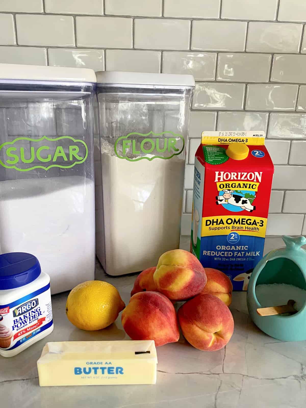 Ingredients on counter: Sugar, flour, baking powder, butter, lemon, peaches, milk, and salt.