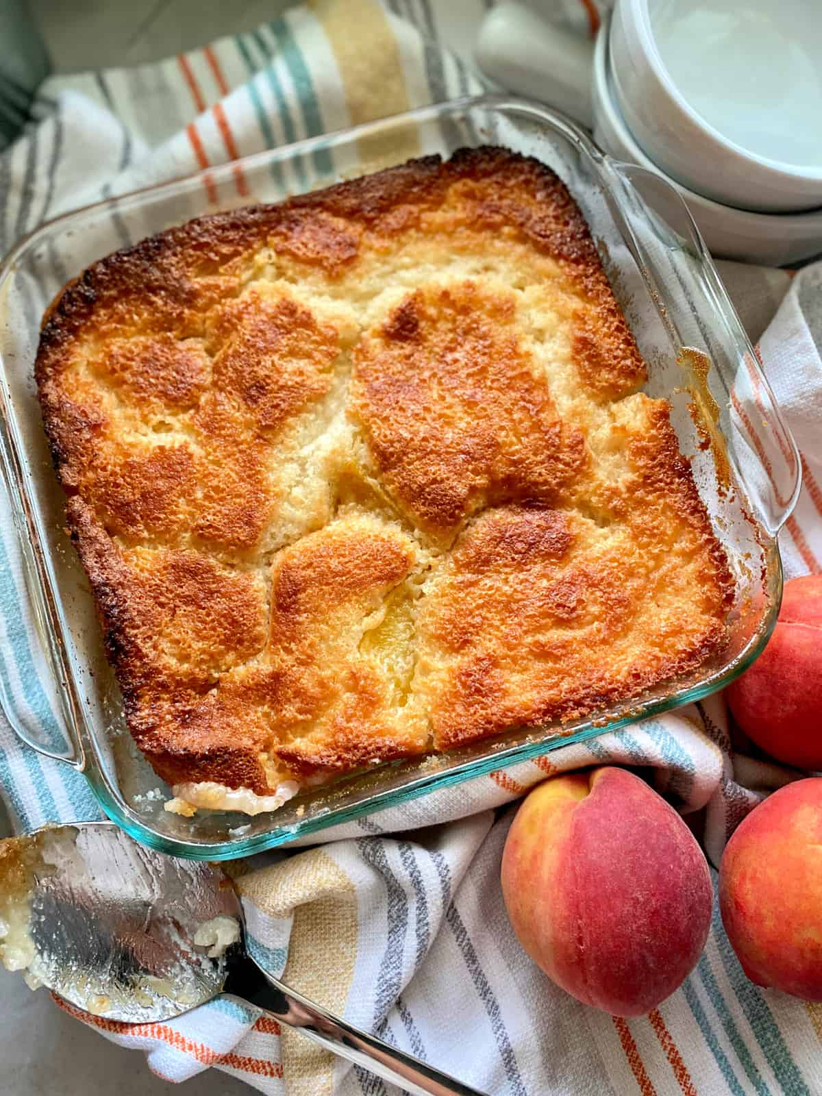 Top view of a square glass baking dish filled with peach cobbler with a spoon and fresh peaches next to it.