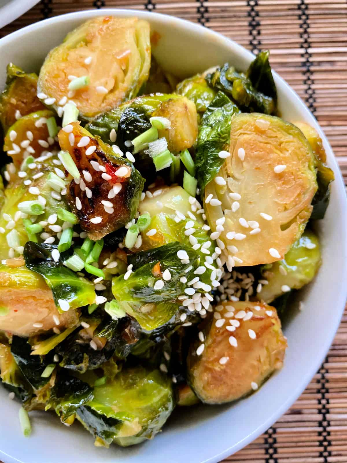 Top view of a white bowl filled with sliced browned brussels sprouts with sesame seeds and green onions.