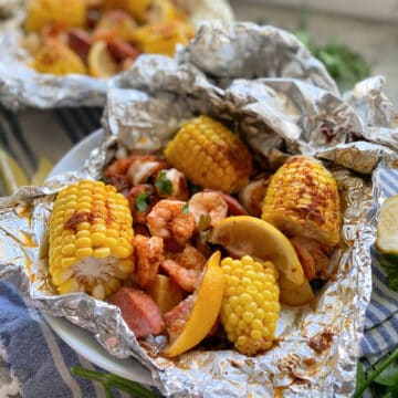 Close up of one foil packet opened with corn, lemon, sausage, and shrimp in a white bowl.