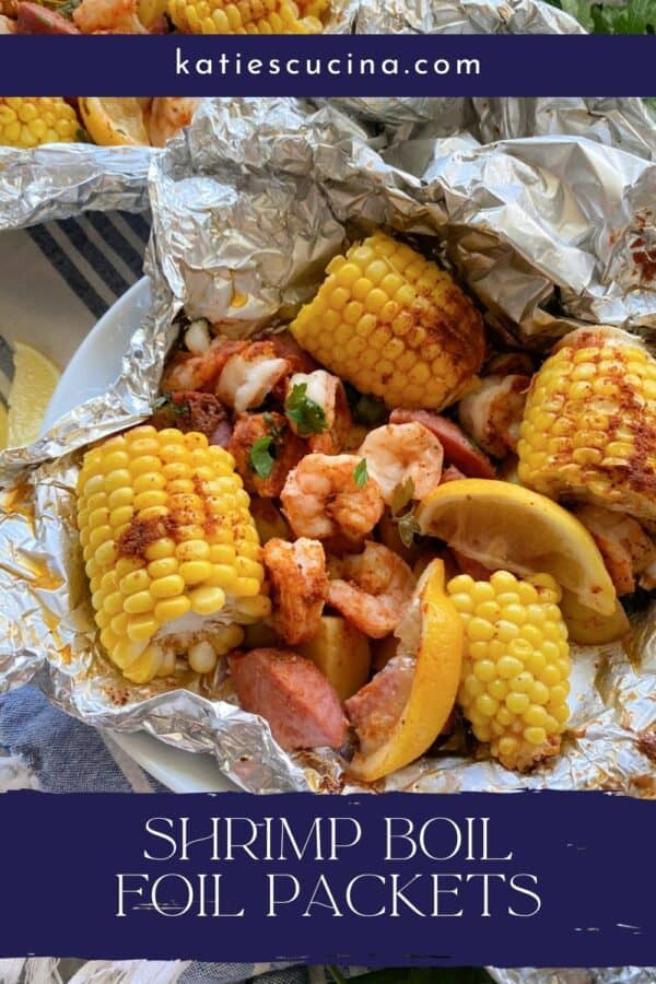 Close up of a foil packet filled with corn, shrimp, sausage, lemon wedges, and potato with text on image for Pinterest.