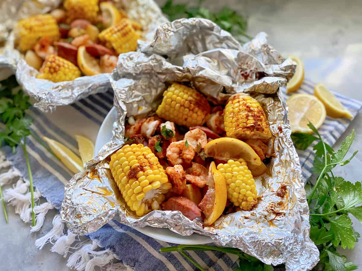 Two foil pouches in a white bowl filled with corn, sausage, shrimp, lemon wedges, and potatoes.