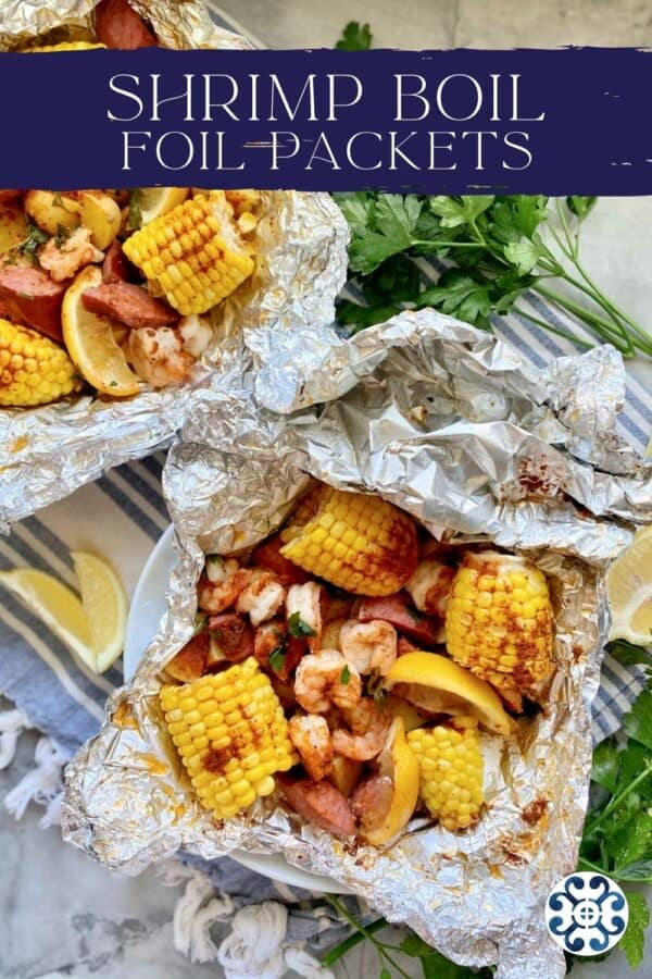 Top view of two foil packets filled with corn, susage, potatoes, shrimp, and lemon wedges with text on image for Pinterest.