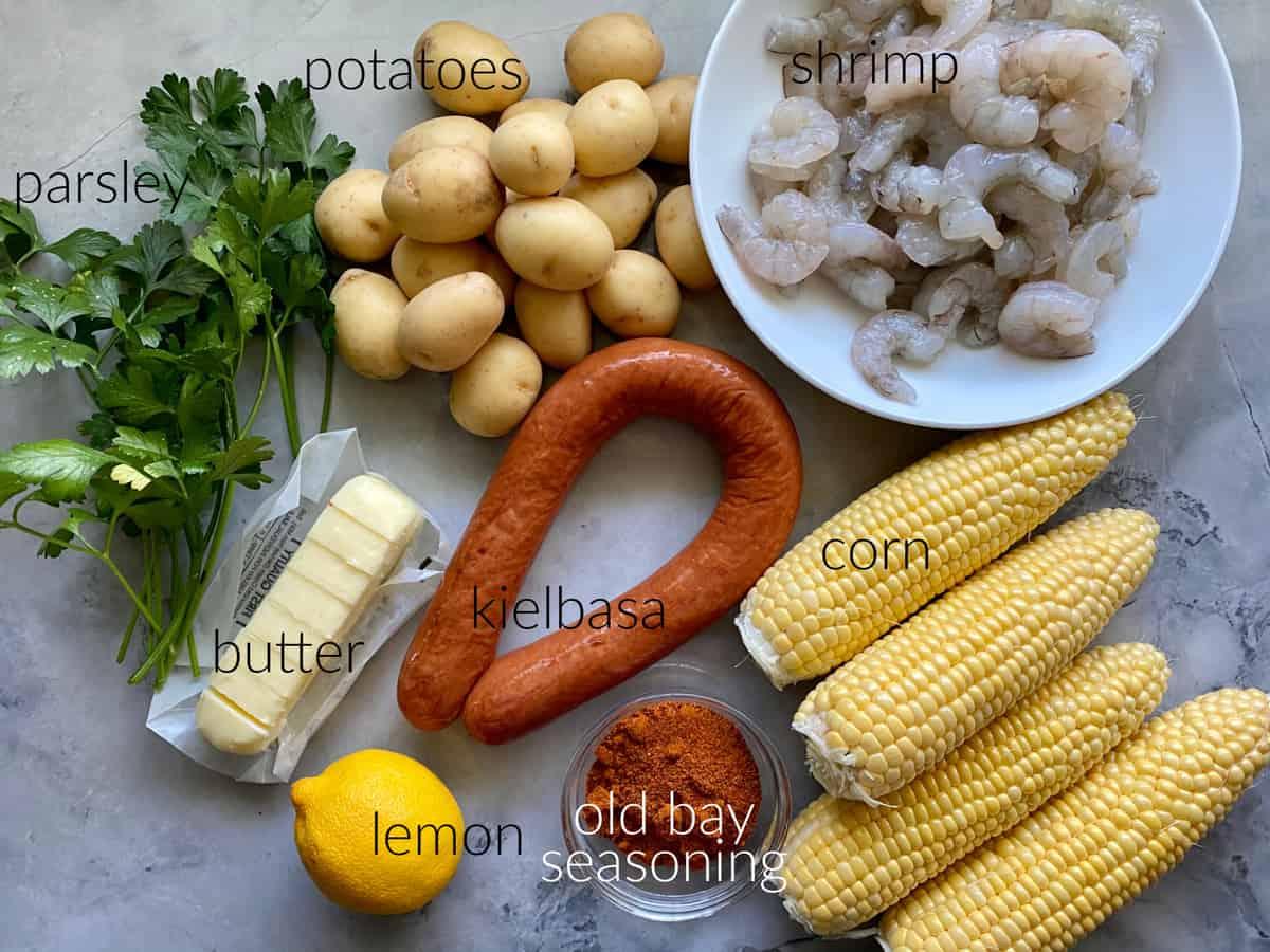 Ingredients: parsley, potatoes, shrimp, butter, kielbasa, corn, old bay seasonning, and lemon.
