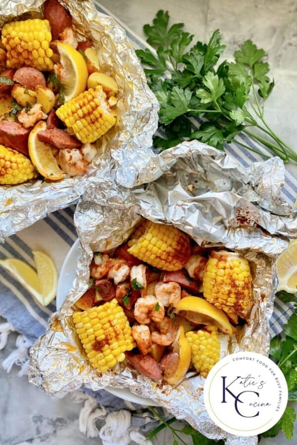 Top view of two foil packets filled with corn, susage, potatoes, shrimp, and lemon wedges.
