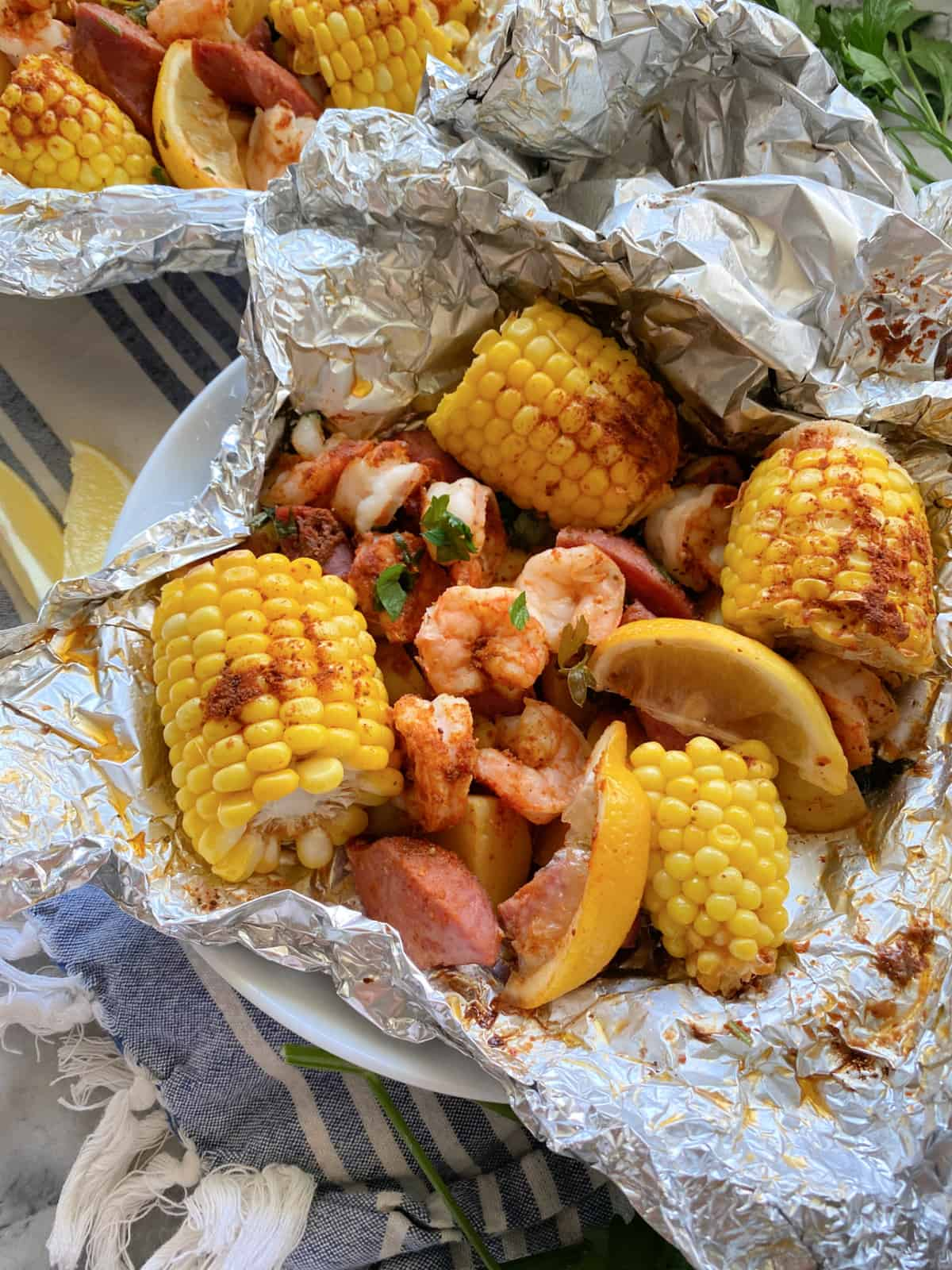 Close up of a white bowl lined with foil with corn on the cob, shrimp, sausage, and lemon wedges.