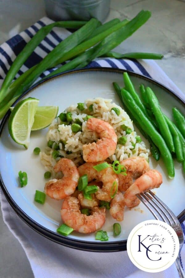 White plate filled with shrimp, green onions, rice, peas, and green beans with logo on right corner.