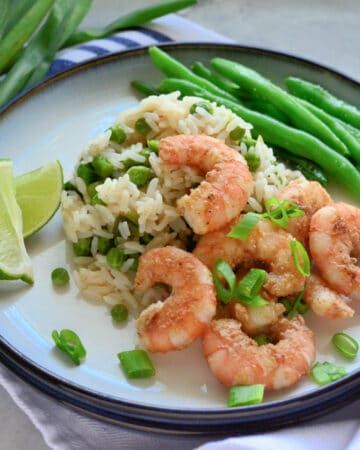 Round white plate with shrimp, rice, green onions and green beans on a plate laying on a cloth.