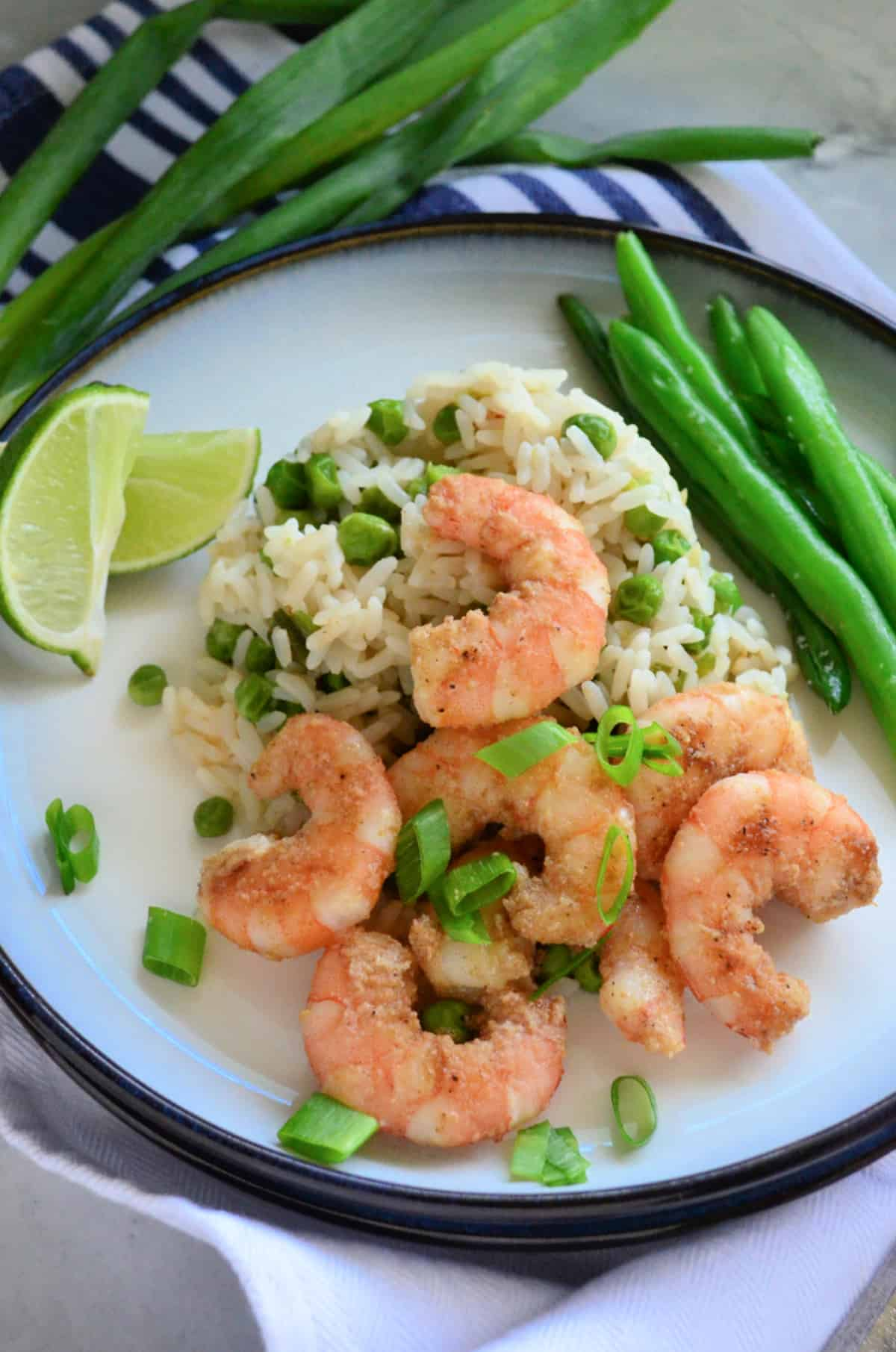 White plate with a blue rim sitting on a counter filled with shrimp, rice, green peas, green onions, and green beans.