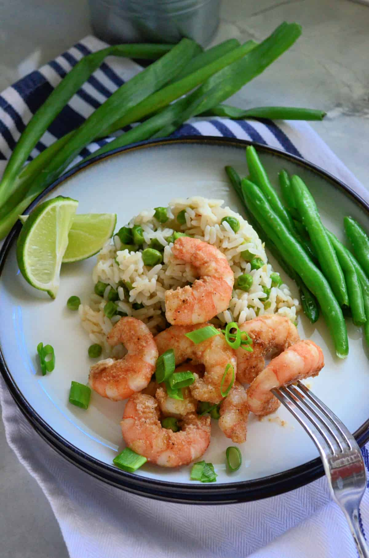 White plate filled with white rice, peas, and shrimp with a fork poking a piece of shrimp.