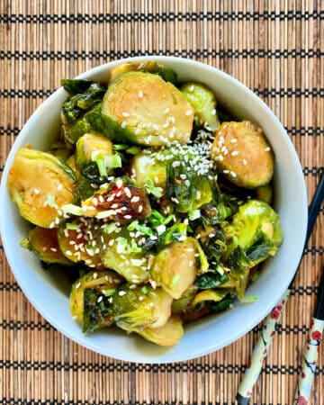Top view of sliced brussel sprouts in a bowl with sesame seeds sprinkled on top with chopsticks next to it.