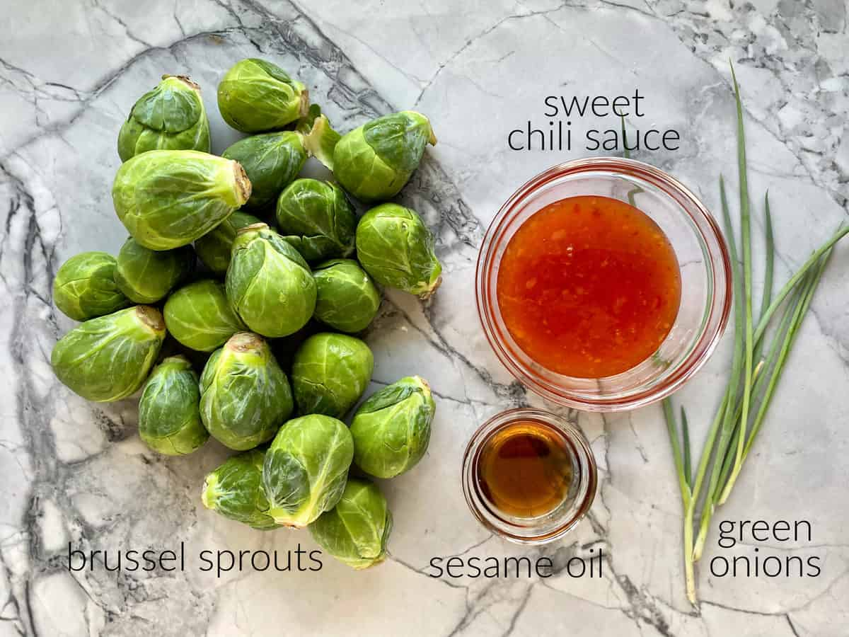 Ingredients on counter; brussel sprouts, sweet chili sauce, sesame oil, and green onions.