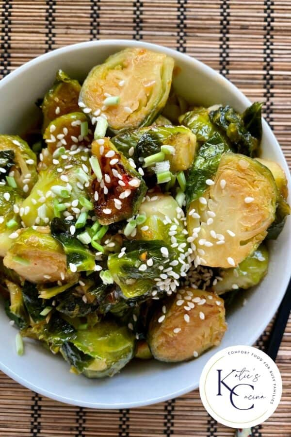 Top view of a bowl filled with sliced brussel sprouts with log on right corner.