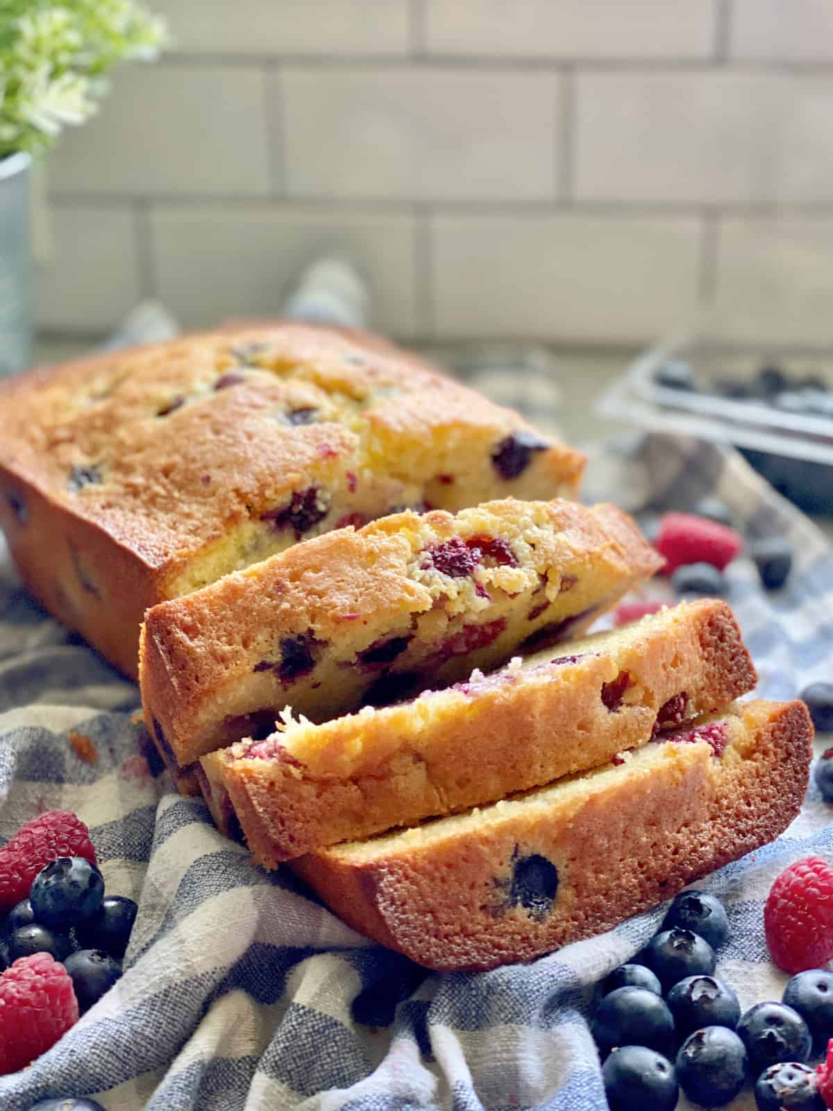 Berry Cornmeal Pound Cake with 3 slices on a white and blue checkered cloth.