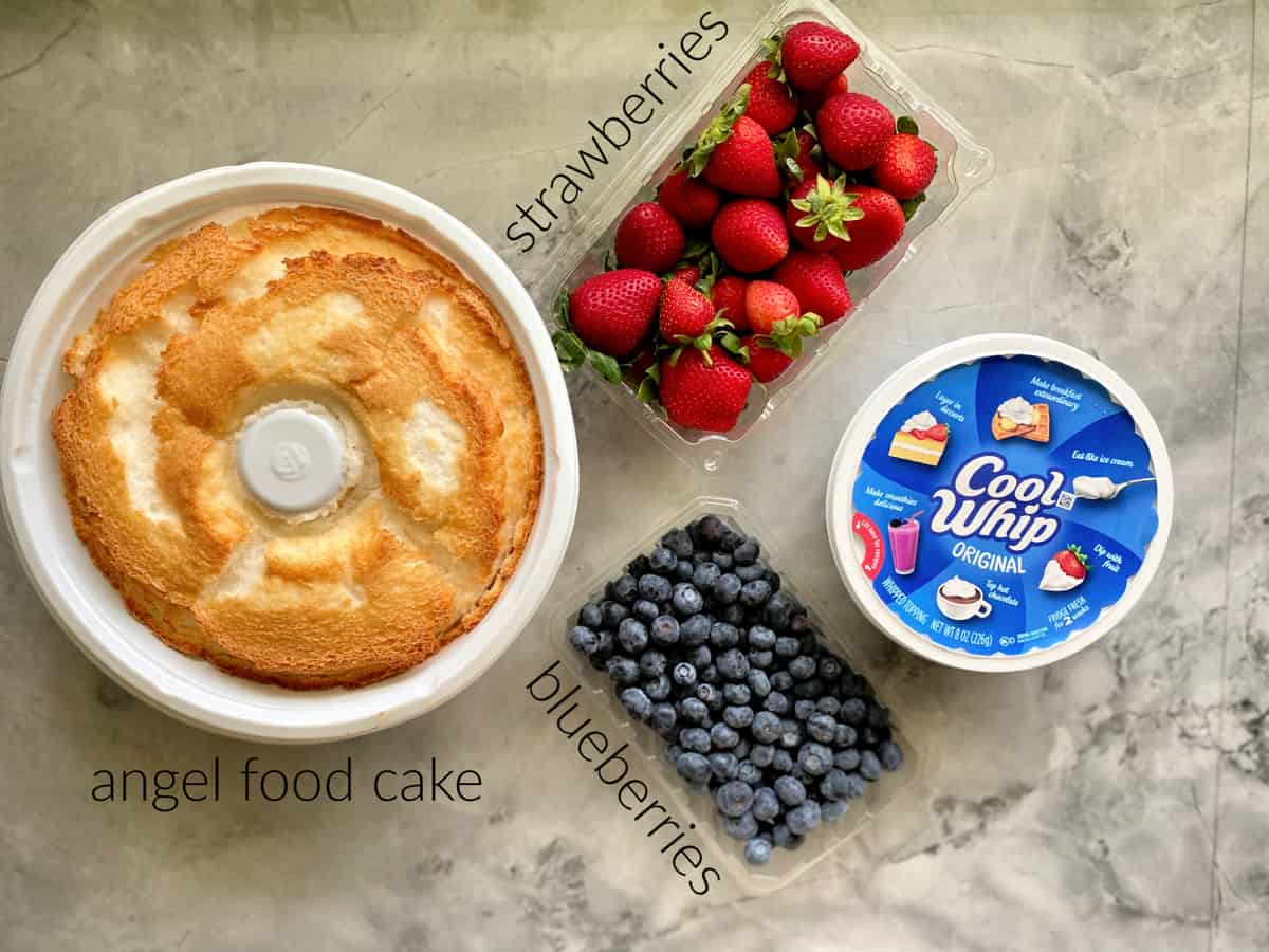 Ingredients on marble countertop: angel food cake, strawberries, blueberries, and Cool Whip