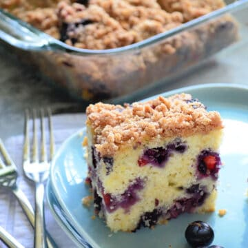 Blue square plate with a slice of Blueberry Coffee Cake with fresh blueberries and a glass baking dish filled with cake in the background.
