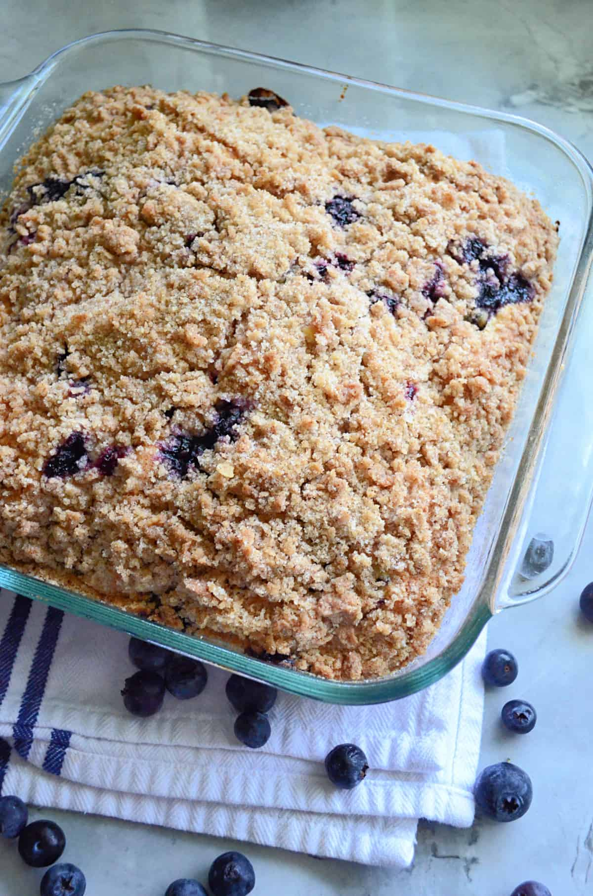 Square glass baking dish filled with a blueberry cake with blueberries on the counter around it.