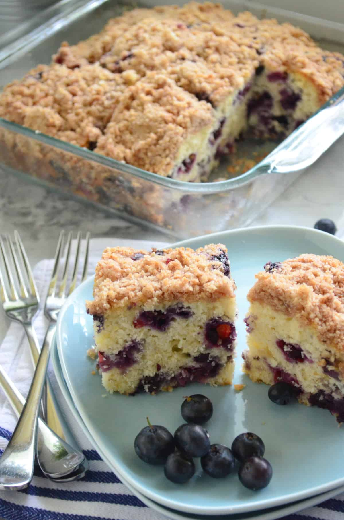 Two slices of Blueberry Coffee Cake with fresh bleuberries on a blue square plate with forks on the side.