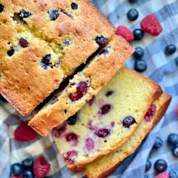 Top view of a Berry Cornmeal Pound Cake with three slices resting on a blue and white checkered cloth.