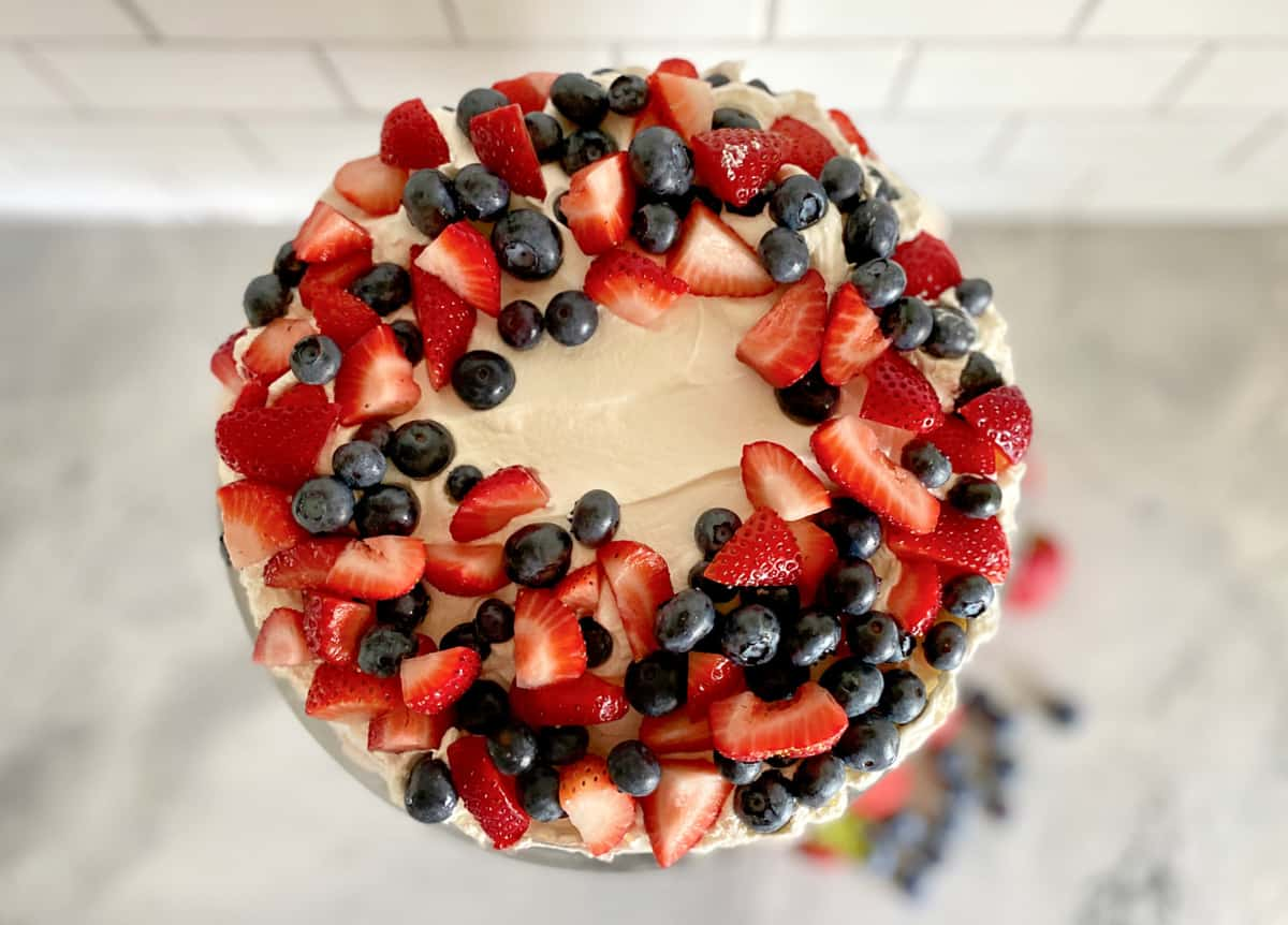 Top view of circle cake filled with chopped strawberries, blueberries, and whipped topping.