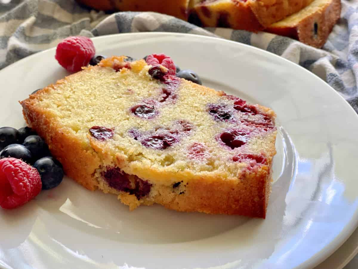 White plate with a slice of Berry Cornmeal Pound Cake with fresh berries.
