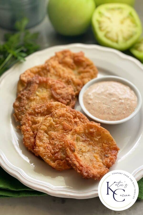 Six golden Fried Green Tomatoes on a white plate with logo on right corner.