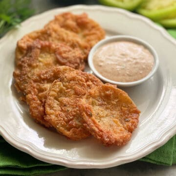6 Fried Green Tomatoes on a white plate with a dipping sauce.