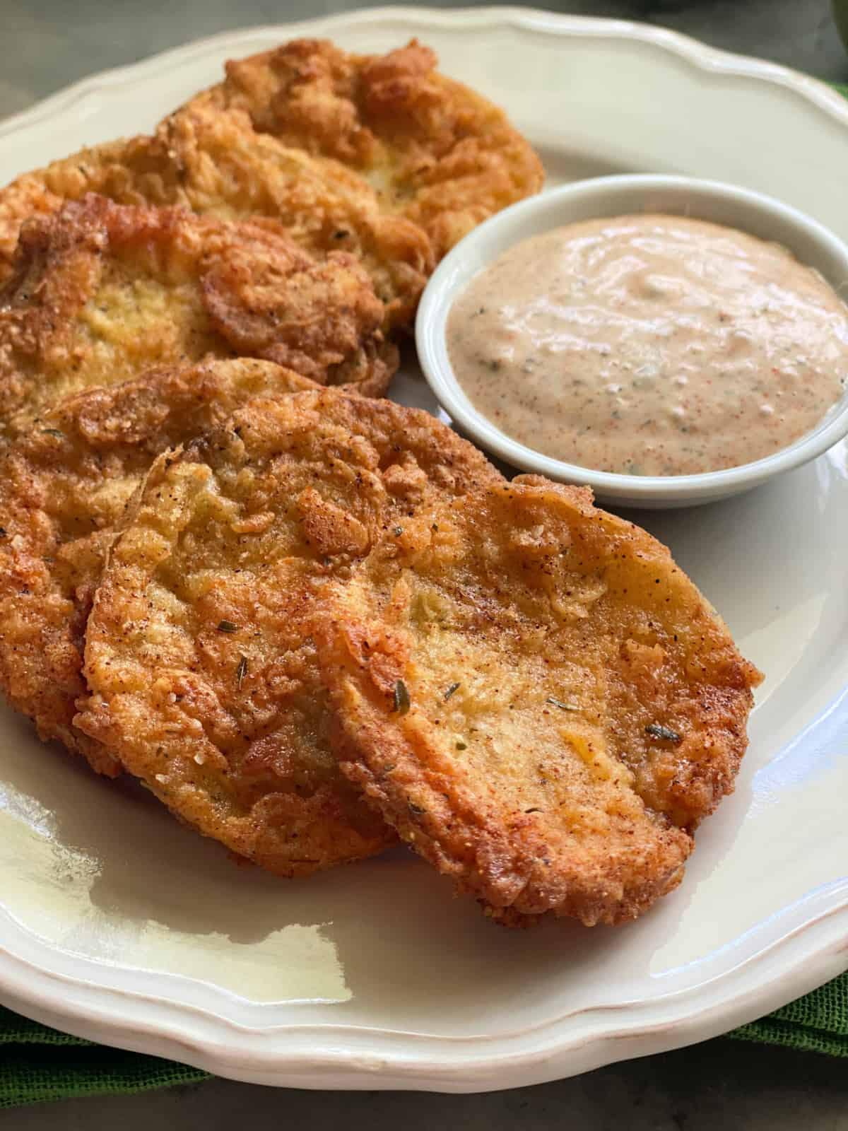 Close up of golden Fried Green Tomatoes on a white plate with ranch dipping sauce.