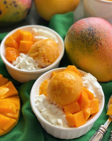 Two white bowls filled with orange frozen yogurt with whipped cream on a dark green cloth.