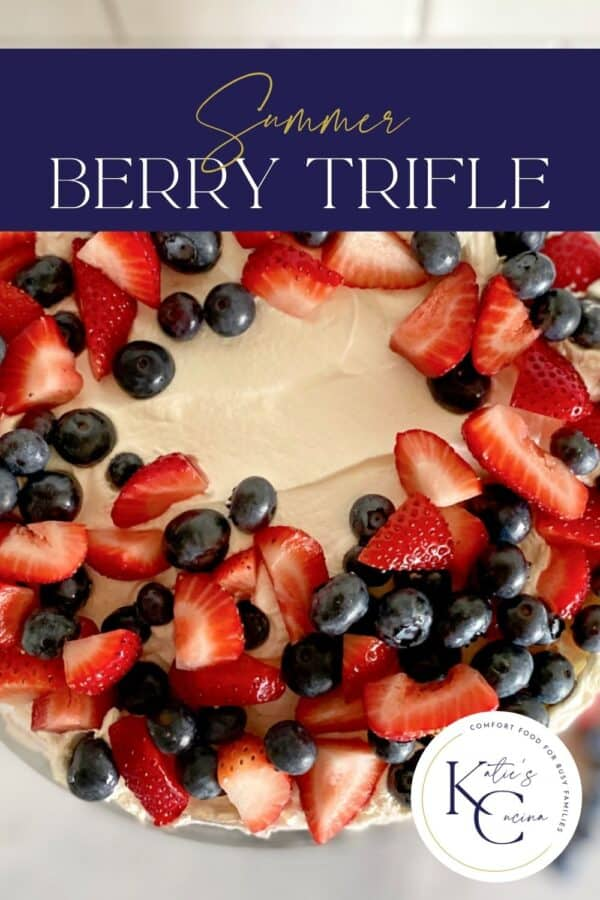 Close up of a cake with whipped topping, chopped strawberries, blueberries with text on image.