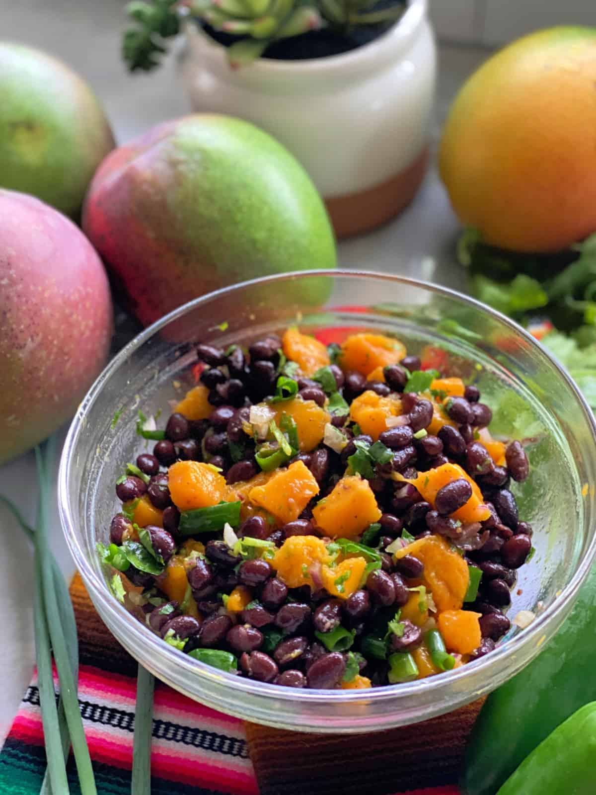 Glass bowl filled with mangos, black beans, and green onion on a multi colored cloth with mangoes in the background.