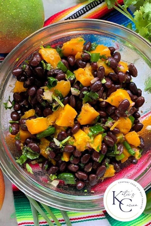 Close up of a glass bowl filled with black bean mango salad with logo on right corner.