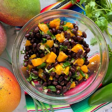 Top view of a bowl filled with black beans and mangoes on top of a kitchen towel with fresh jalapenos and manges.