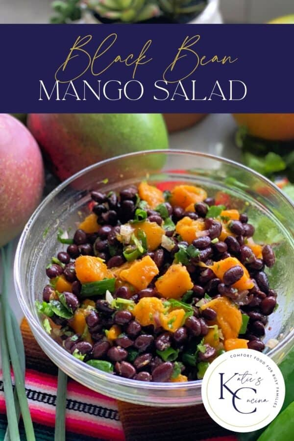 Glass bowl filled with black beans, mango, and green onion with recipe title text on image for Pinterest.