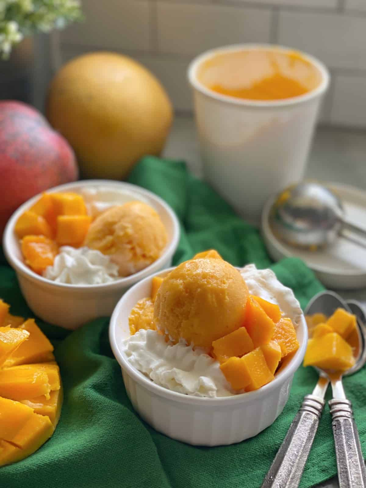 Two white bowls filled with Mango Frozen Yogurt on a green cloth with spoons and mangoes on the counter.