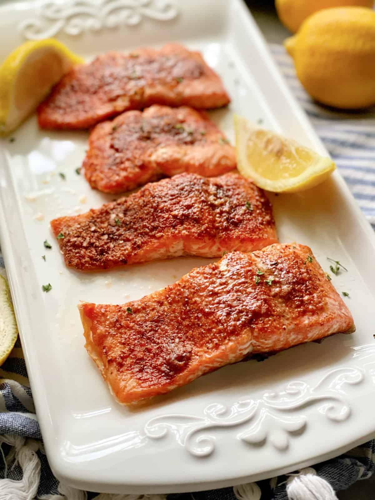 White platter filled with 4 seasoned salmon filets with lemon wedges on platter.
