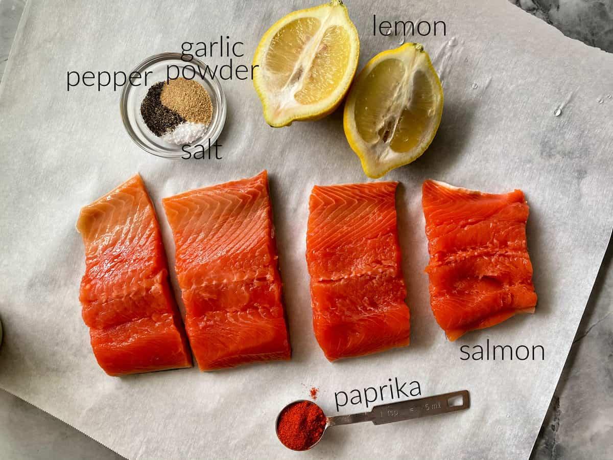 Ingredients on white parchment paper: salmon, paprika, salt, pepper, garlic powder, and lemon.